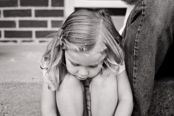 Young girl looking at the ground
