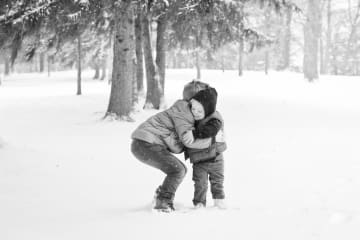 young brothers embrace in the snow in Missouri
