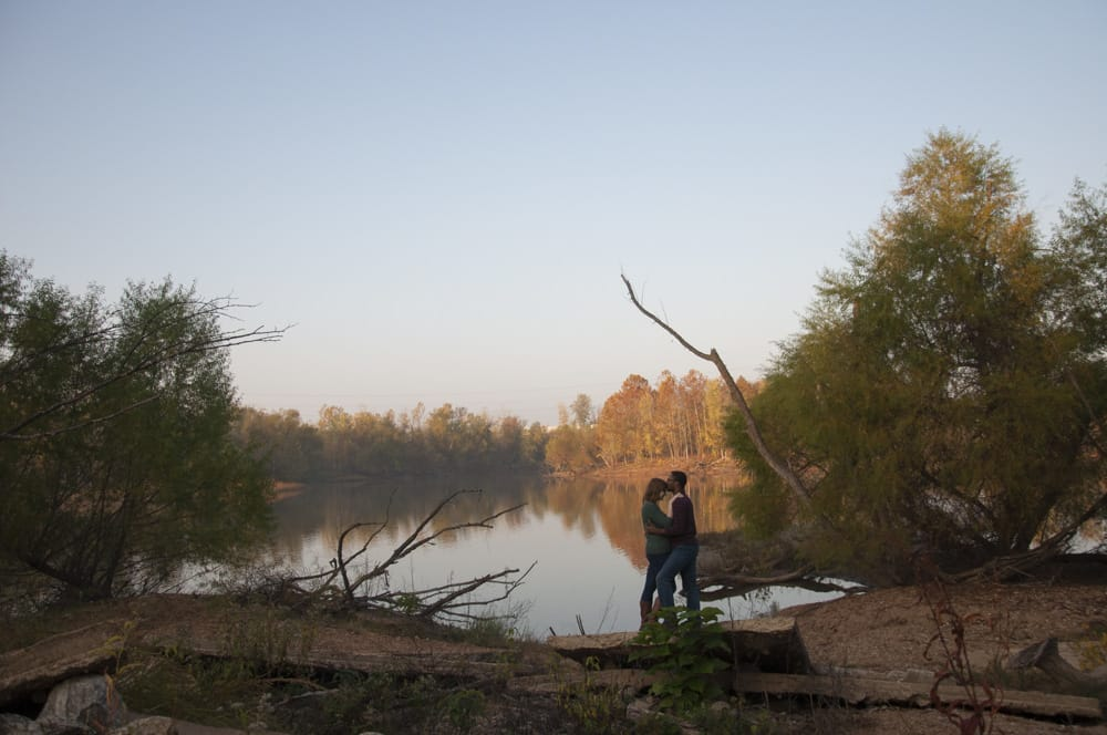 Multiracial couple with black man and white woman kissing near lake in Unger Park in South or West County