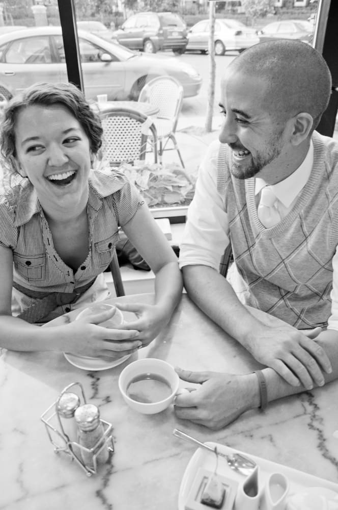 photograph of engaged couple laughing over coffee in Central West End in St. Louis
