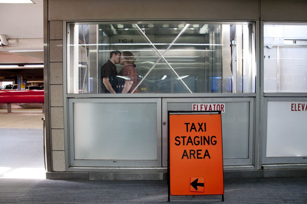 couple kissing in Saint Louis Lambert Airport elevator near taxi staging area in the parking garage