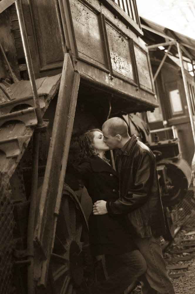 couple kissing near old train at Museum of Transportation in West County Saint Louis