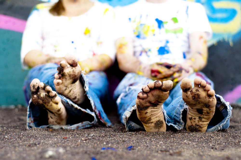 picture of dirty feet and paint splatters at grafitti wall in STL with engaged couple