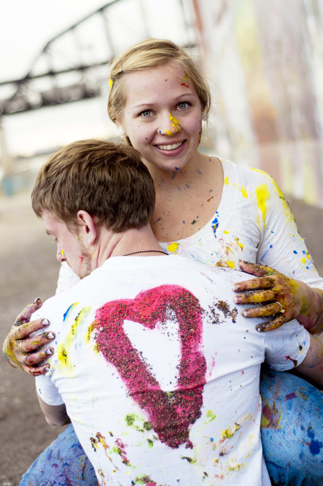Engagement couple at grafitti wall in STL riverfront area with paint and gravel