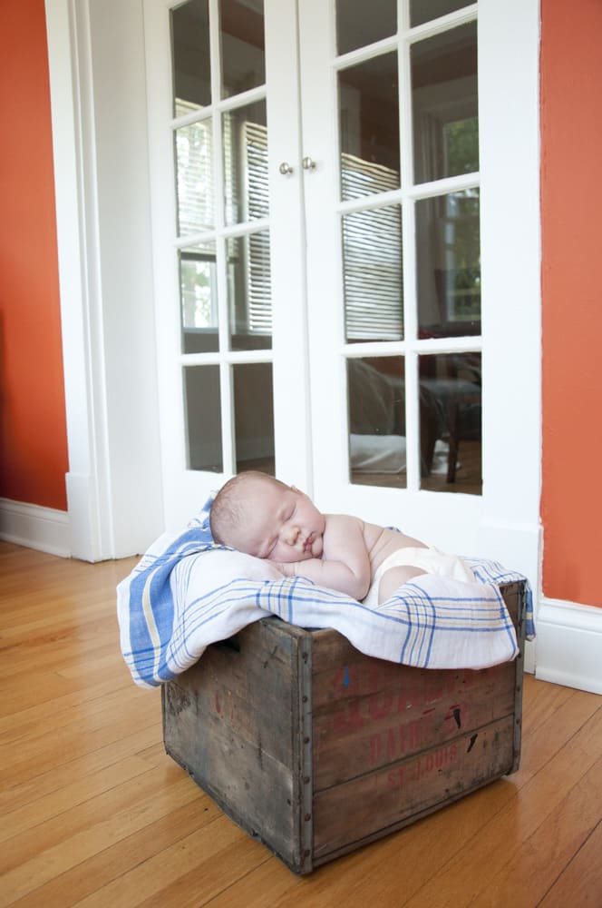 portrait of infant boy asleep in a weathered crate