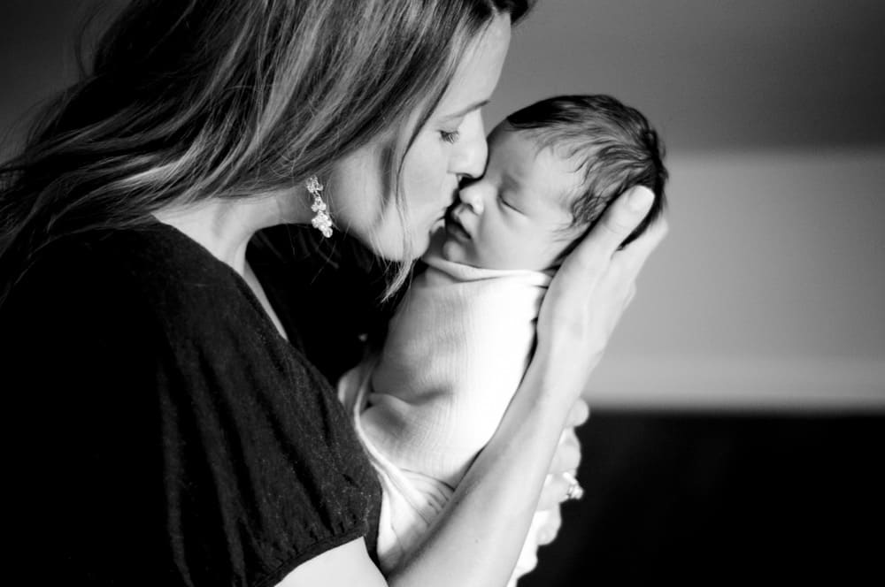 mother kissing her newborn son in black and white photograph