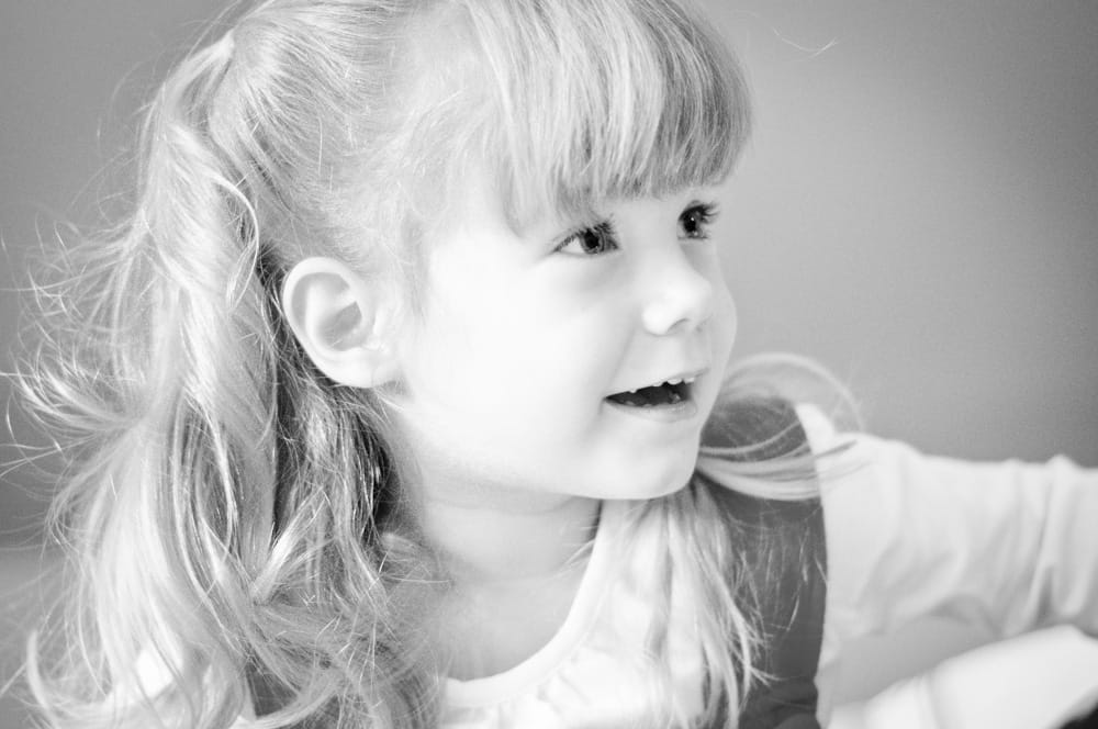 toddler girl smiling in black and white photograph