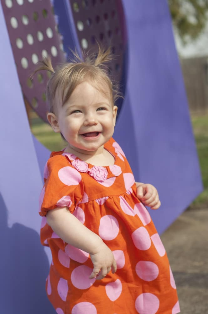 Smiling toddler girl with polka dots and pigtails in South County St. Louis