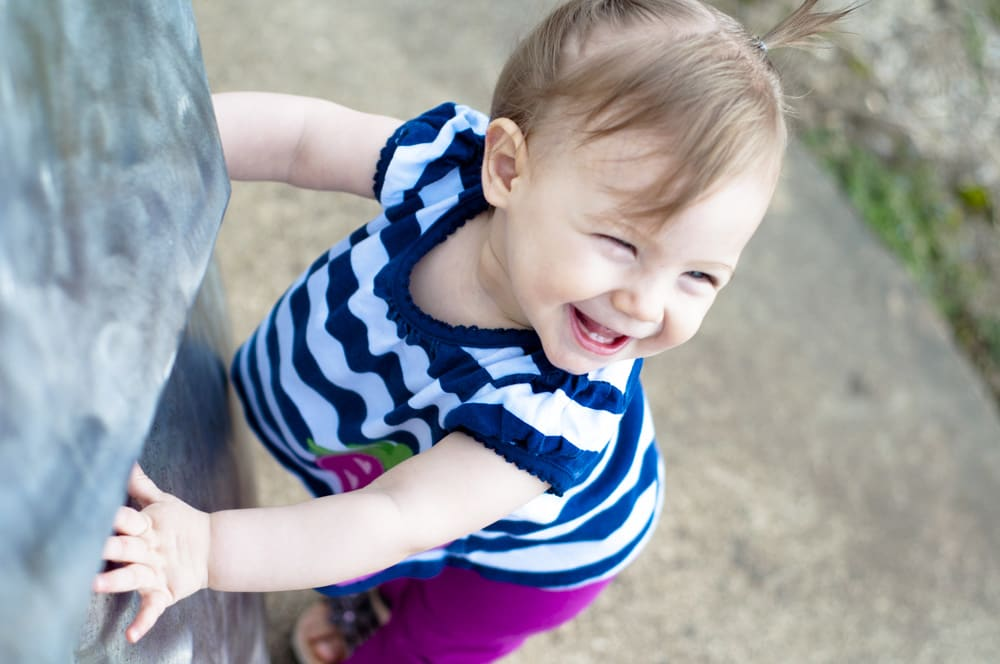 one-year-old girl smiling outdoors