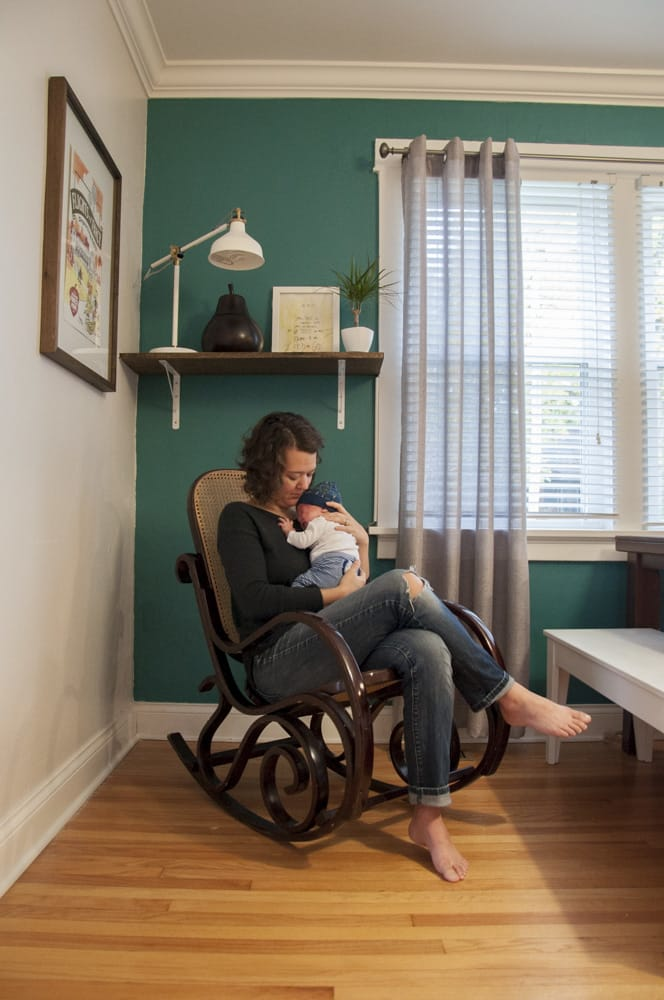 mother in rocking chair soothing her newborn baby boy