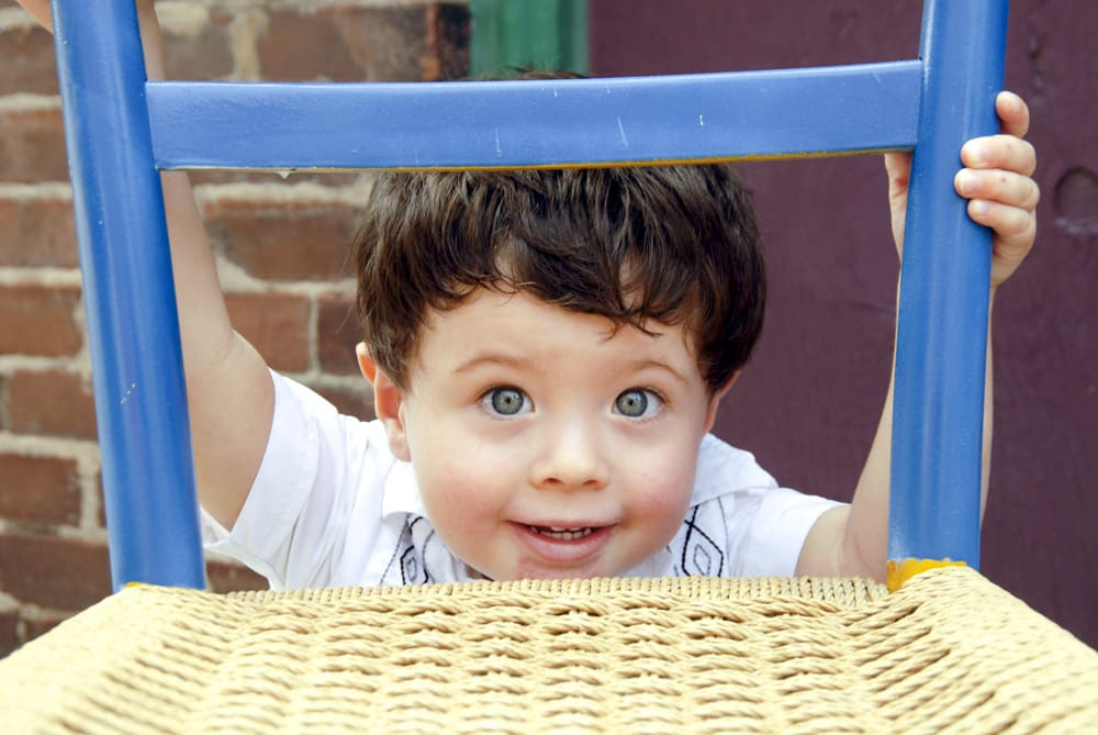 picture of toddler boy with big eyes looking through a chair