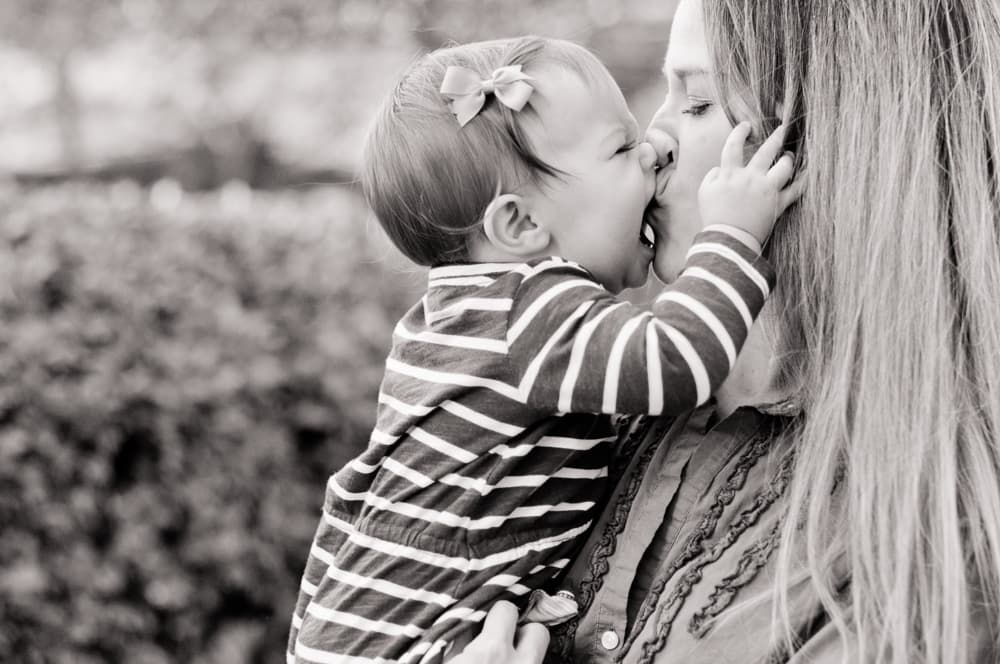 baby girl kissing her mother