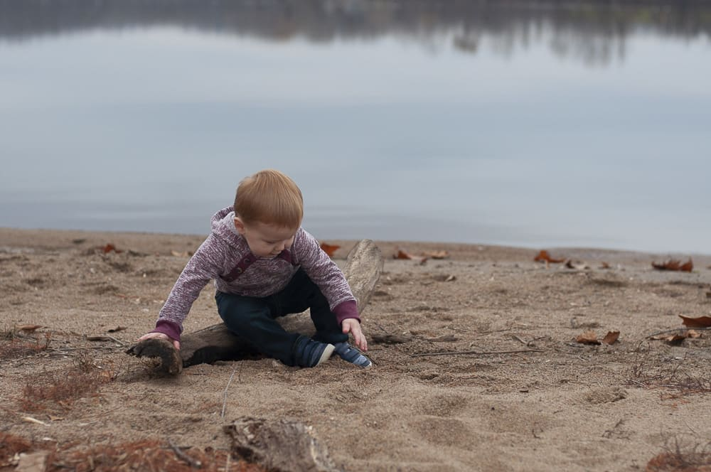 young boy sitting on the beach of Creve Couer Lake in St. Louis Mo