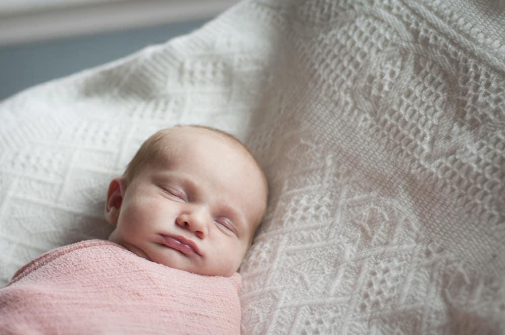 photo of newborn girl wrapped in pink