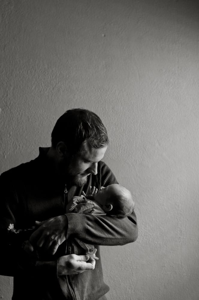 Father holds his newborn baby