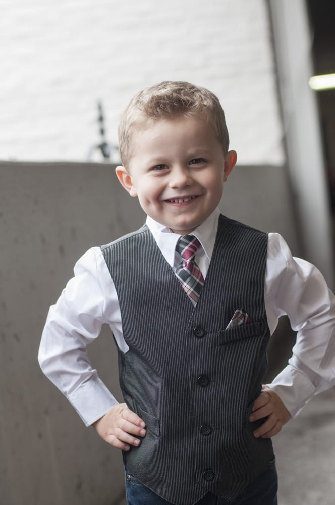 toddler boy in vest and tie with dimples