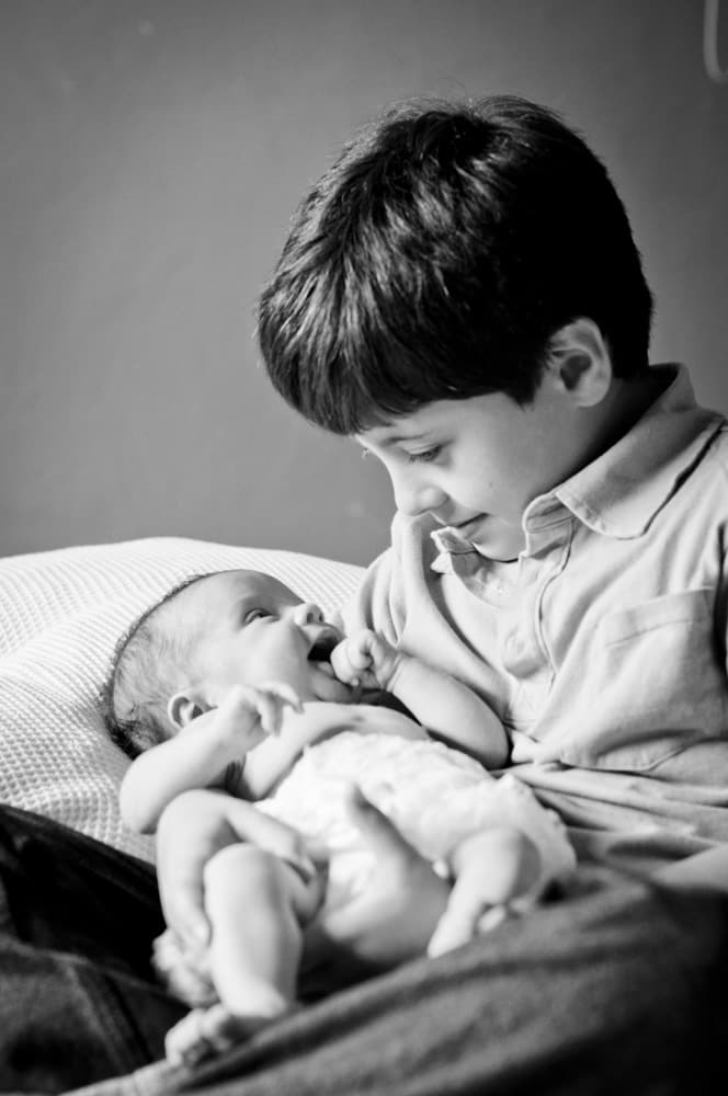 Big brother holding a newborn baby girl in black and white picture