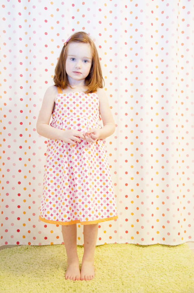 young girl in polkadots matches her poilkadotted shower curtain in New Town, St. Charles, MO