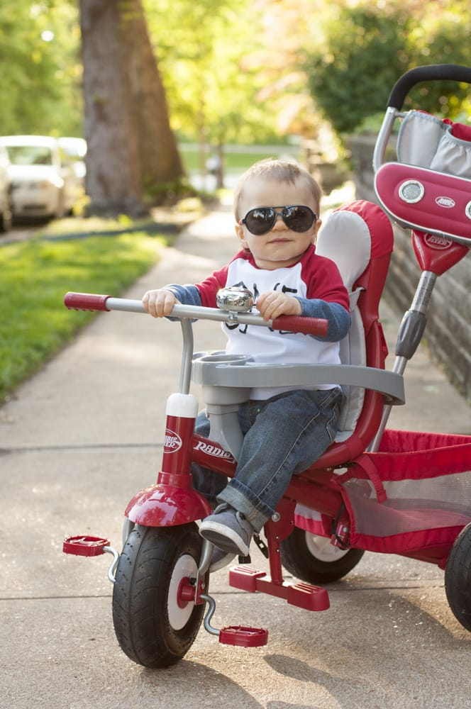photograph of one year old baby on radio flyer tricycle with aviator sunglasses near Forest Park in St. Louis
