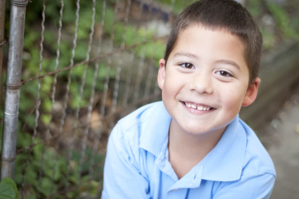 boy smiling by fence and ivy in blue shirt