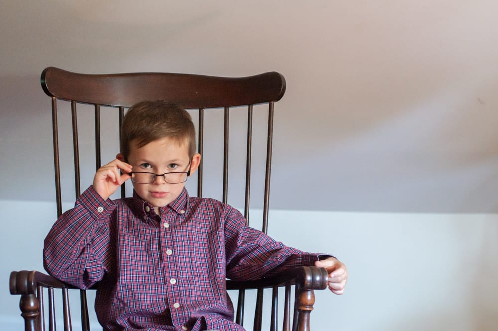 young boy in rocking chair with glasses looking like an old man