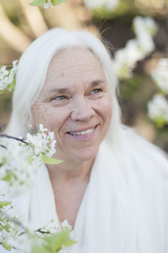 Portrait of an older, mature woman with long white hair and bradford pear blooms
