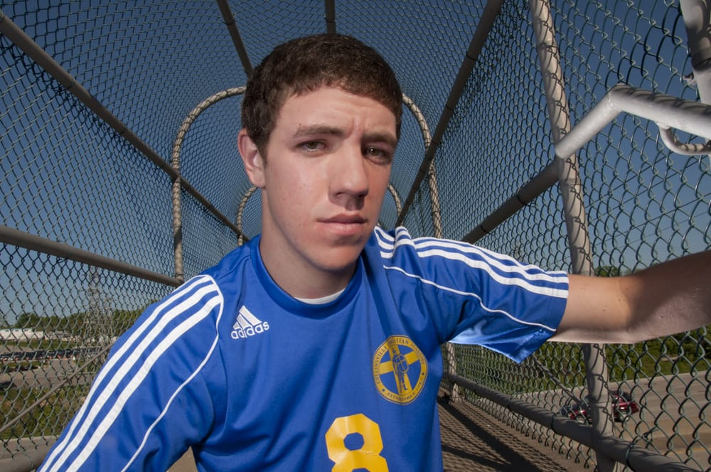 High School Senior Boy with soccer jersey portrait on overpass with blue sky in North County St. Louis