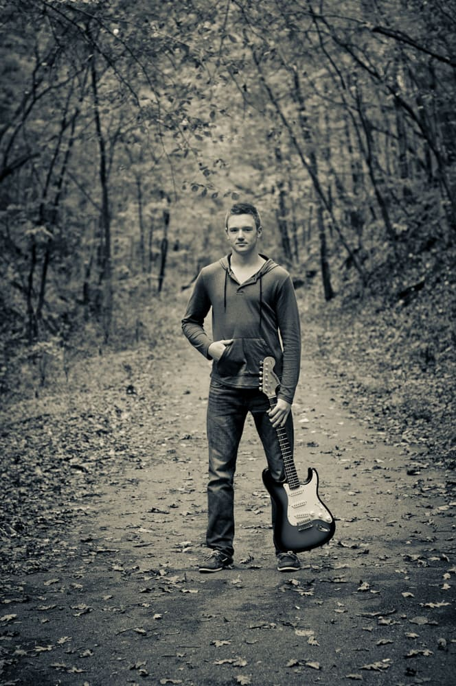 High School Male senior picture with guitar on trail in West County, St. Louis