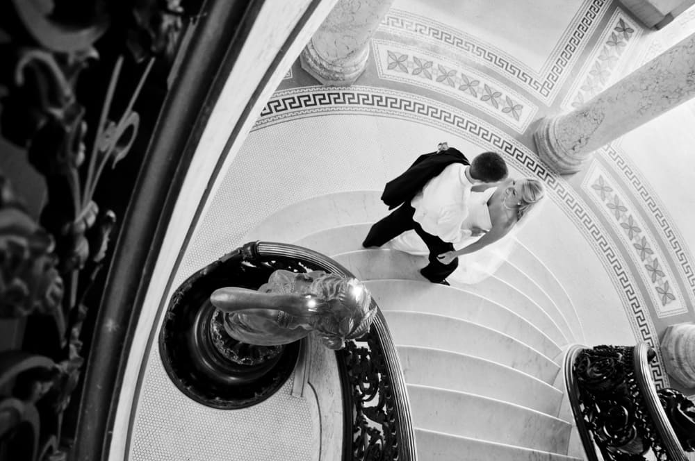 Bride and Groom standing at in the entryway of the University City City Hall in black and white
