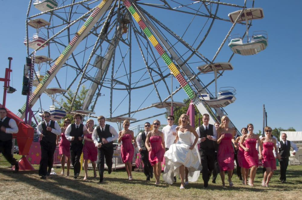 Wedding Party running at the photographer at a summer carnival for july fourth with bright colors