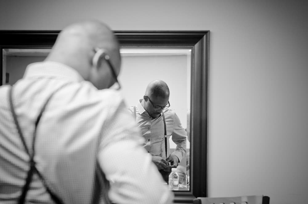 Afrian American groom adjusted suspenders before wedding ceremony in St. Peter's MO