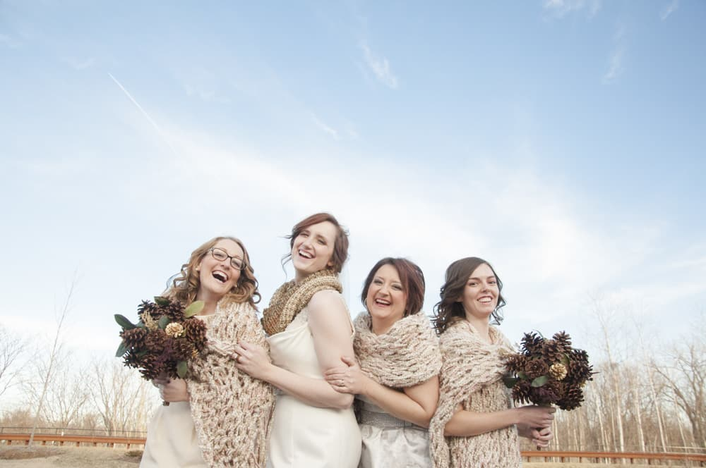 Bridesmaids and bride laughing with shawls and scarves on winter wedding day outdoors