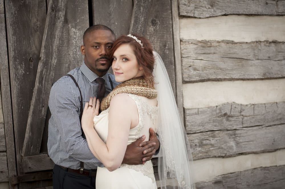 Black groom with suspenders and white bride with scarf and veil hug at log cabin in St. Peters