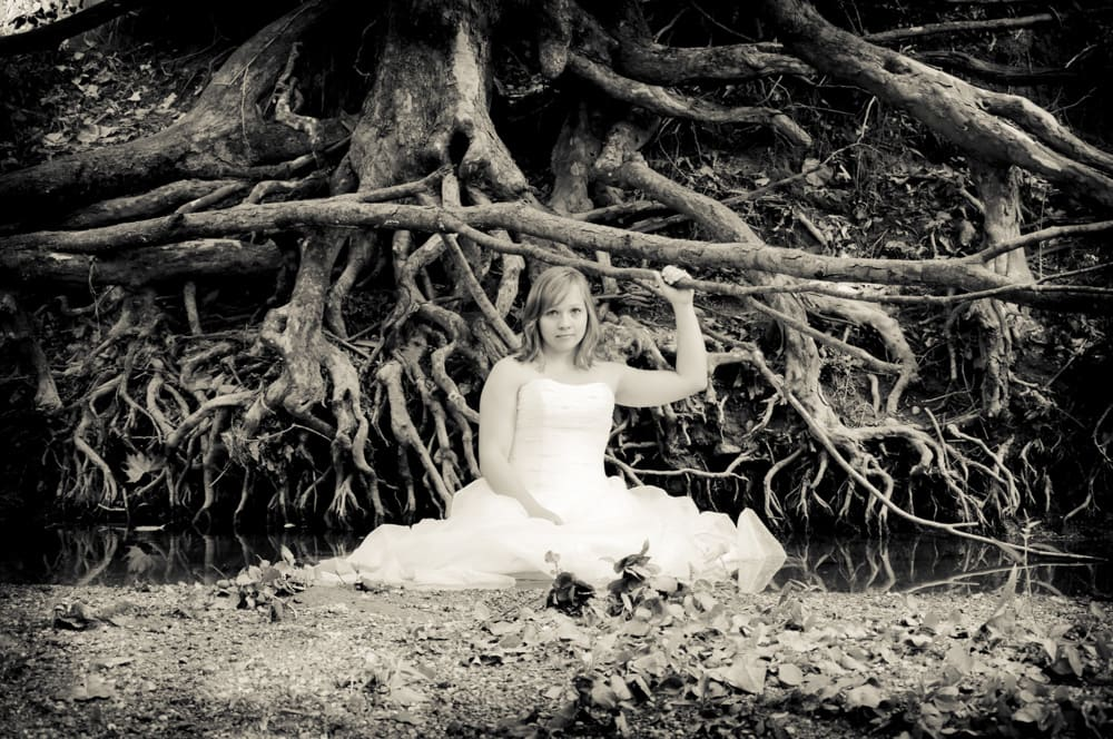 Bride by tree roots in a creek for a trash the dress session in Illinois