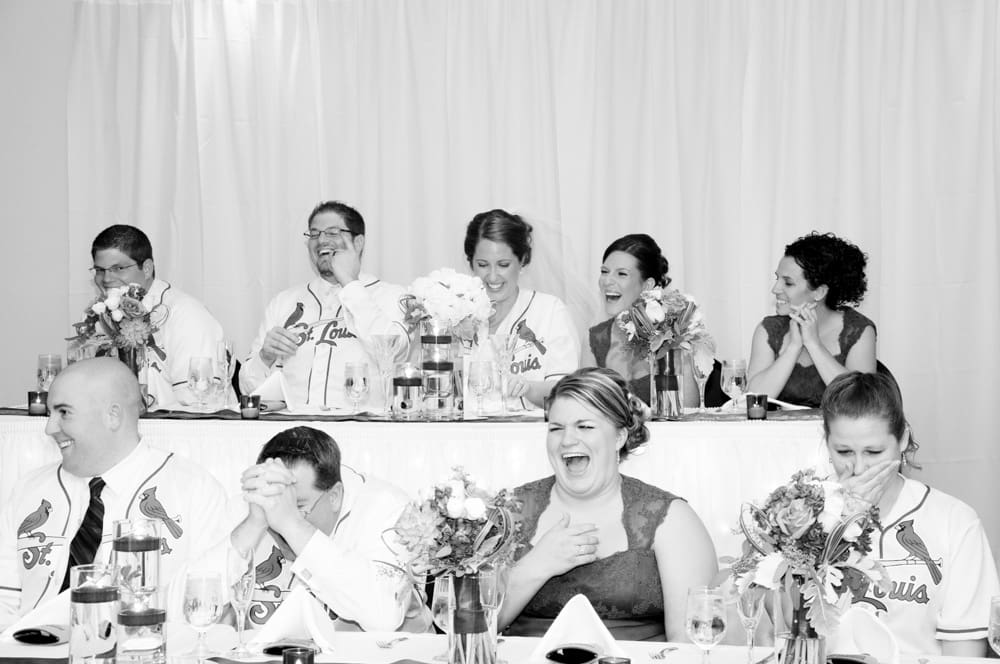 bridal party in St Louis Cardinal's jersies cracking up at a joke during toasts in STL
