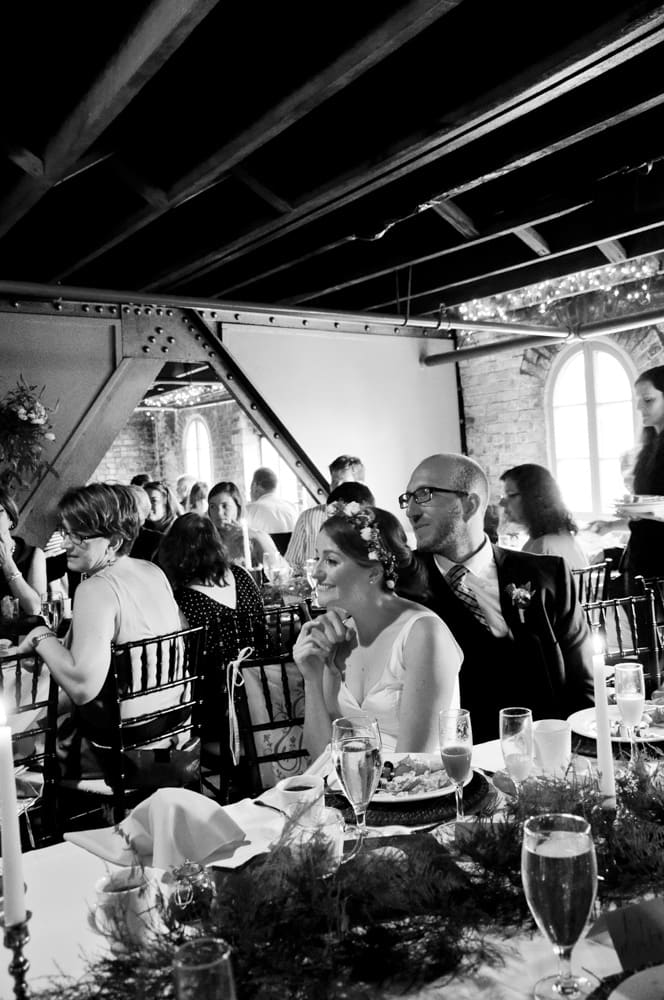 Bride and Groom sitting among guests listening to their toasts in a unique venue in Cherokee district