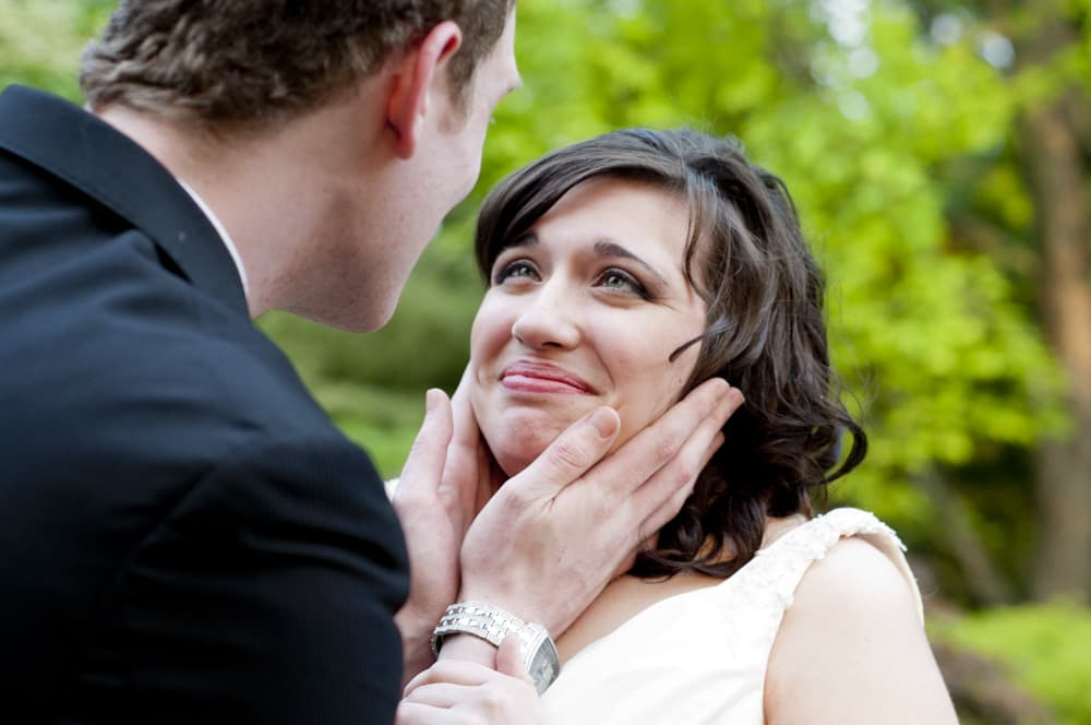 Groom cupping brides chin while she looks emotional at the Conservatory