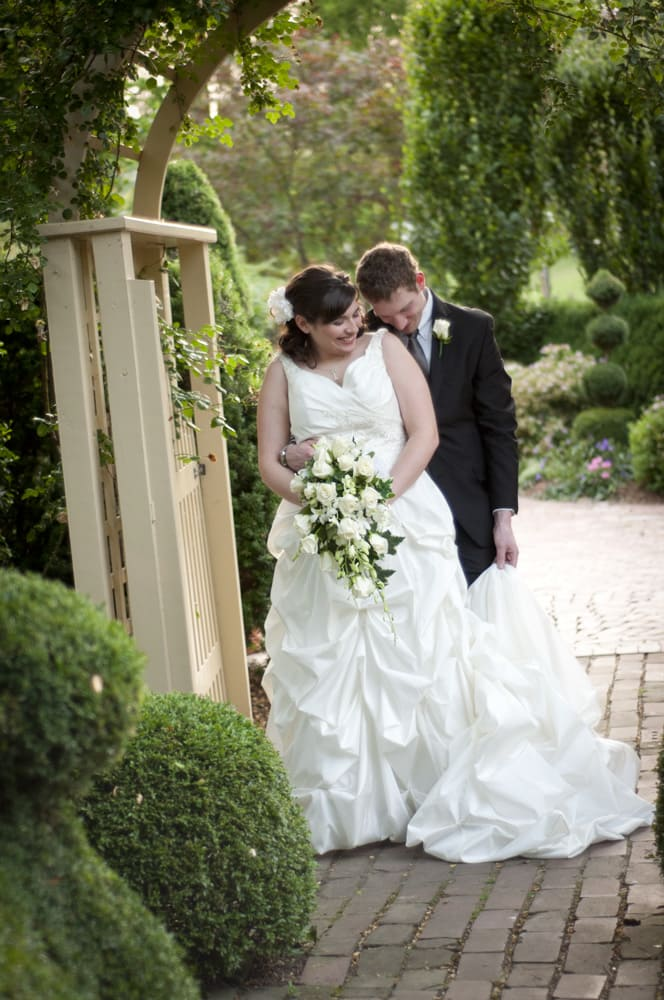 Giggling bride and groom in a garden at the Conservatory in St. Charles MO