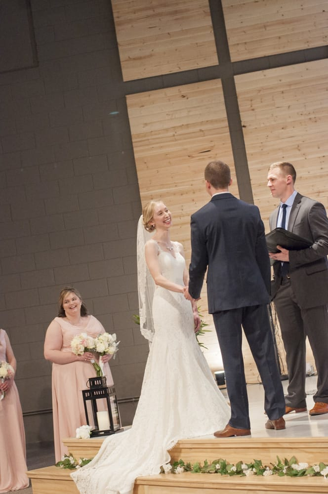 Bride laughing with groom during wedding vows in U City church in St. Louis