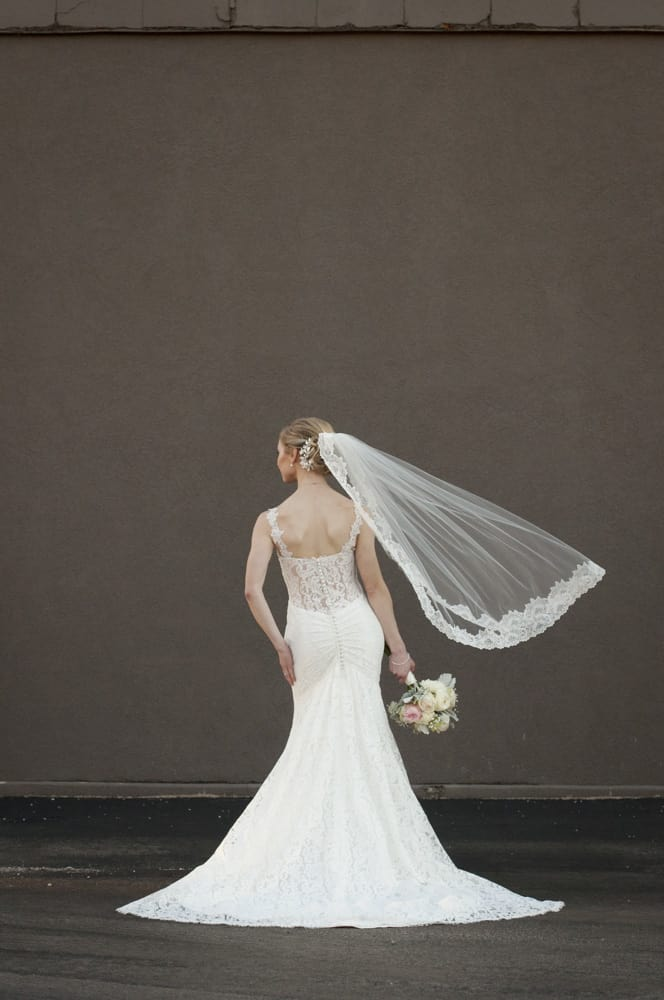 fashion pose of bride with gray wall and veil in the wind in St. Louis