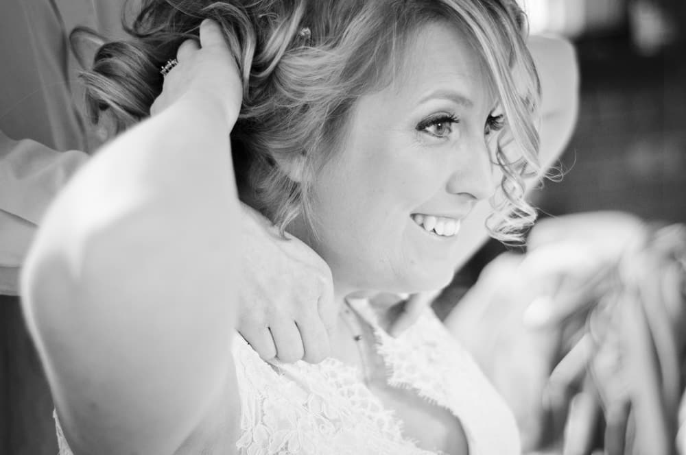 Bride having jewlery adjusted before her wedding in Soulard MO
