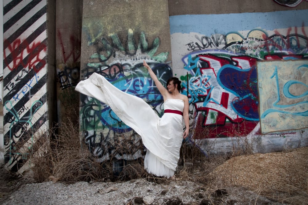 Trash the dress tossing train high in the hair with the wind at grafitti wall
