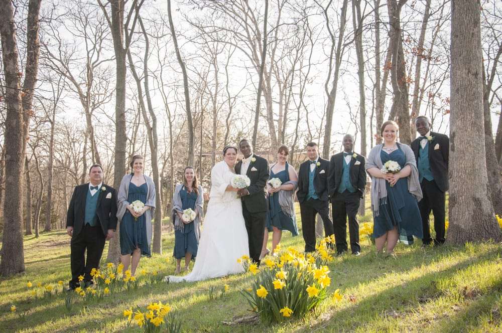 Multiracial bridal party with daffodils and blue dresses and shawls