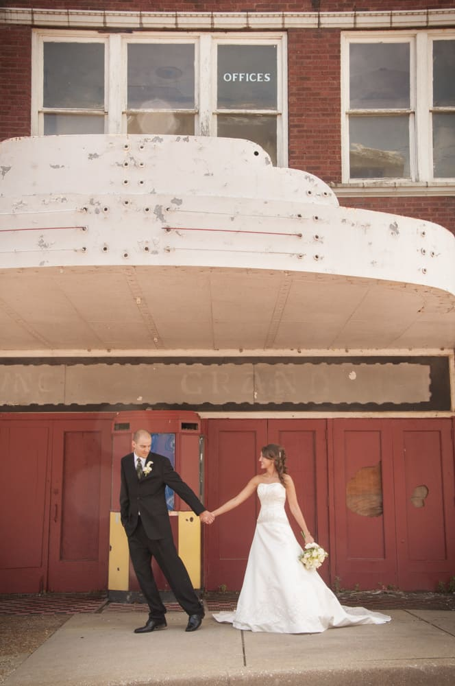 Groom leading bride in front of a histroric theater in Alton IL