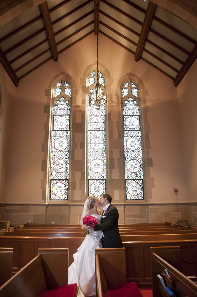 Bride and Groom kissing in tradtional church in Clayton MO
