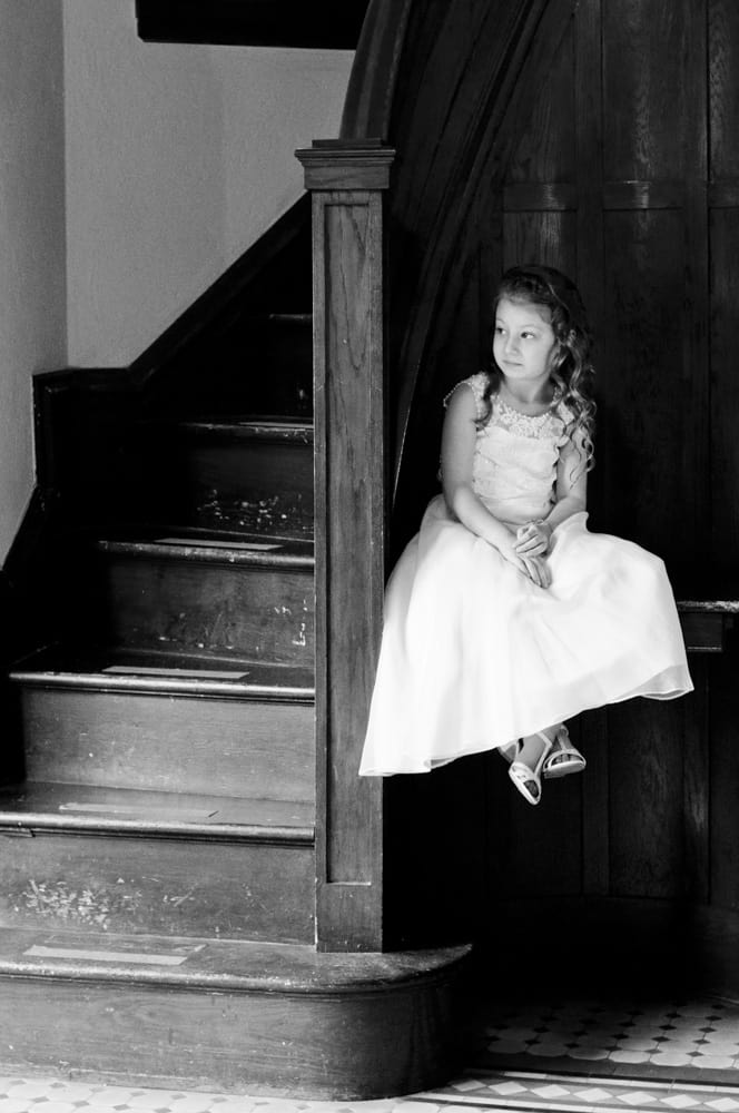 Flower girl looking out the door while sitting on a ledge