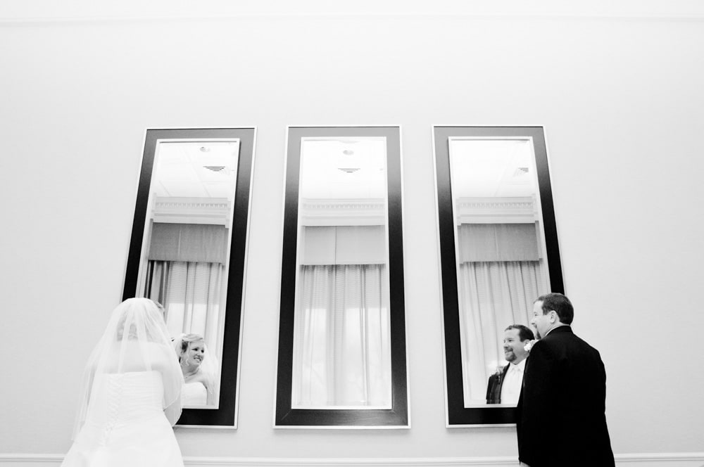 Couple looking in mirrors at hotel in Central West End for a spring wedding on a rainy day