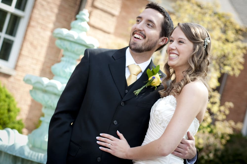 bride and groom smiling at their wedding party on a spring day in Florissant MO near a fountain at City Hall