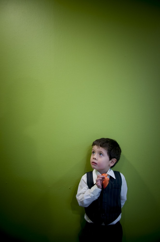 ring bearer adjusting orange tie by green wall in U City MO