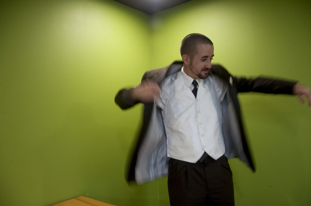 groom putting his wedding suit coat on against a green wall in U City MO